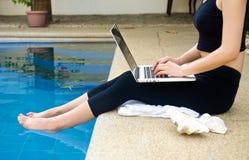 Flickaarbete med bärbara datorn på pölen Royaltyfri Bild
