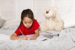 Flickaattraktioner för litet barn med blyertspennor hemma arkivbilder