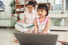 flickabärbar dator little som leker royaltyfri fotografi