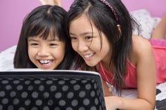 flickabärbar dator little som leker två Royaltyfri Fotografi
