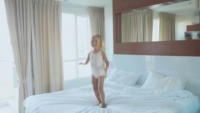 Flickabanhoppning för litet barn på säng i ultrarapid på sovrummet på morgonen stock video