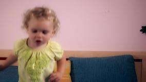 Flickabanhoppning för hyperaktivt barn på säng i sovrum arkivfilmer