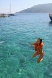 Flickabanhoppning in i vattnet Arkivfoton