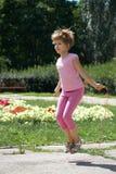 Flickabanhoppning på ett överhopprep i parkera Arkivbild