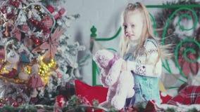 Flickabanhoppning på sängen med en leksak i henne händer Isolat på vit stock video
