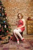 Flickabarn i röd klänning på julgranen Royaltyfri Foto