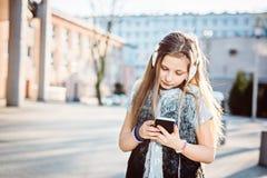 Flickabarnet lyssnar till musiken från hennes smartphone Arkivbild