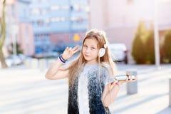Flickabarnet lyssnar till musiken från hennes smartphone Arkivbilder