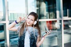 Flickabarnet lyssnar till musiken från hennes smartphone Royaltyfri Bild