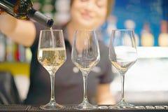 Flickabartendern häller vin in i ett vinexponeringsglas royaltyfria bilder