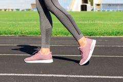 Flickaben i rosa sportskor som står på ett rinnande spår med stadionställningar Sportar och sunt begrepp royaltyfria foton