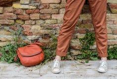 Flickaben står nära en tegelstenvägg, hipsterstil Royaltyfria Bilder