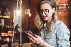 Flickabloggeren i moderiktiga exponeringsglas sitter i kafé och använder smartphonen, kontrollerar mejl, meddelar med anhängare,  arkivfoto
