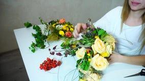 Flickablomsterhandlaren väljer upp blommor för bukett för brud` s och skapar blom- arbetssammanträde på tabellen i regeringsställ stock video