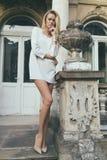 Flickablondin mot bakgrunden av en gammal husarkitektur Royaltyfri Fotografi