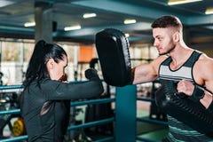 Flickaboxaredrev lagledaren rymmer att boxas fokusblock övande skott för idrottsman nen i idrottshallen fotografering för bildbyråer