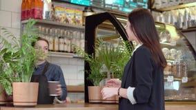 Flickabrunetten får kaffe från baristaen och med att le går ut stock video