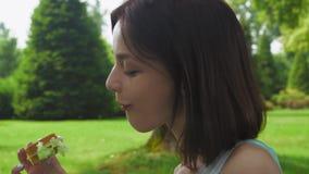 Flickabrunettsammanträde i parkera och äter en smörgås med sallad close upp stock video