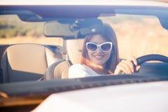 Flickachauffören sitter bak hjulet av en cabriolet Arkivfoton