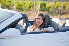 Flickachauffören sitter bak hjulet av en cabriolet Arkivbild