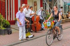 Flickacyklist med blommor och gatamusiker (Buskers) nära ca royaltyfri fotografi