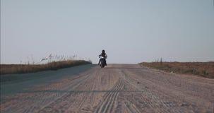 Flickacyklisten rider en motorcykel över den främre sikten för horisonten arkivfilmer