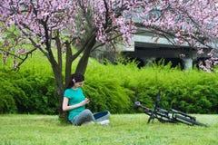 Flickacyklisten vilar under ett träd royaltyfri bild