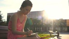 Flickadanandeanmärkningar på solnedgången i strålar av solen och att skriva ner henne hopp och drömmar av framtid in i hennes dag arkivfilmer