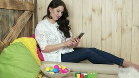 Flickadanandefoto av den vide- plattan mycket av easter ägg och att le den unga kvinnan som photoshooting stock video