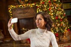 Flickadanandeselfie med julgranen Royaltyfri Fotografi