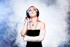Flickadans med den brutna armen och hörlurar Royaltyfri Fotografi