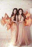 flickadeltagare två Härliga unga kvinnor i eleganta guld- dres Royaltyfria Foton