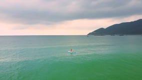 Flickadiagramet ligger på paddleboarden som driver bland det azura havet lager videofilmer