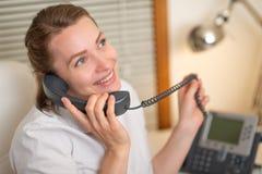 Flickadispatcheren arbetar med telefonen I appellmitten royaltyfri bild