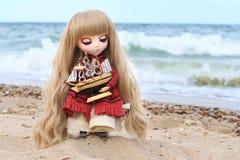 Flickadocka med det långa blonda innehavet ett litet skepp på stranden Royaltyfria Bilder