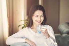 Flickadricksvatten som hemma sitter på en soffa royaltyfri foto