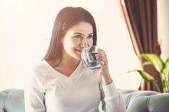 Flickadricksvatten som hemma sitter på en soffa royaltyfria bilder