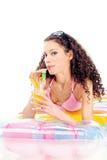Flickadrinkfruktsaft på luftmadrassen Arkivbild