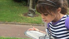 Flickadrinkvatten från att dricka springbrunnen arkivfilmer