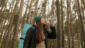 Flickadrinkvatten från en flaska på bakgrunden skogen arkivfilmer