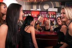Flickaföretag som har gyckel i nattklubben Royaltyfri Foto