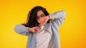 Flickaflyttningar till rytmen av musik Woamn med dans för lockigt hår på gul bakgrund Kvinnlig som har gyckel Henne som ler lager videofilmer