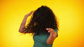 Flickaflyttningar till rytmen av musik Woamn med dans för lockigt hår på gul bakgrund Kvinnlig som har gyckel Henne som ler arkivfilmer
