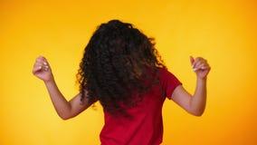 Flickaflyttningar till rytmen av musik Woamn med dans f?r lockigt h?r p? gul bakgrund Kvinnlig som har gyckel Henne som ler stock video