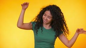 Flickaflyttningar till rytmen av musik Woamn med dans f?r lockigt h?r p? gul bakgrund Kvinnlig som har gyckel Henne som ler lager videofilmer