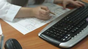 Flickaformgivaren arbetar på datoren och fläckarna på de pappers- planjusteringarna stock video