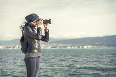 Flickafotografen tar foto eller video nära havet fotografering för bildbyråer