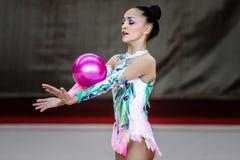Flickagymnasten utför med en boll på konkurrensen Royaltyfri Fotografi