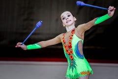 Flickagymnasten utför med klubbor på konkurrensen Arkivfoto