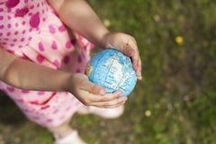 Flickahänder som rymmer jorden Royaltyfri Fotografi